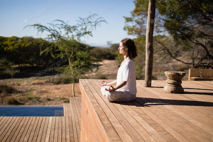 Woman practicing yoga on wooden plank