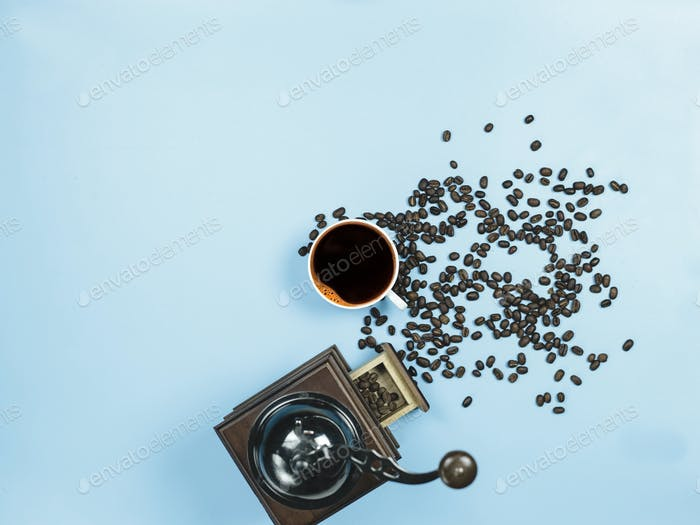 top view black coffee and coffee grinder on blue background