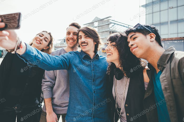 Group of young multiethnic friends taking a selfie with smart ph