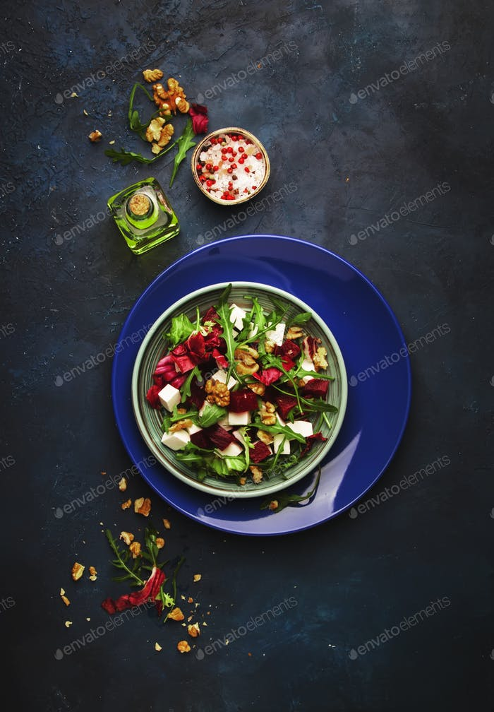 Arugula, Beet and cheese salad with fresh radicchio and walnuts on plate