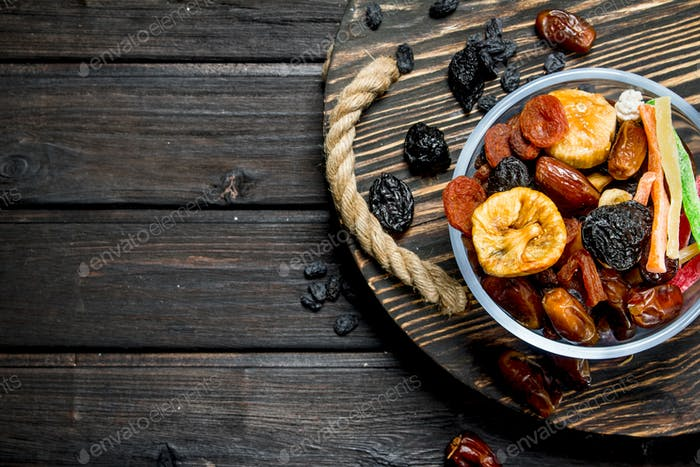 Assortment of different dried fruits in bowl.