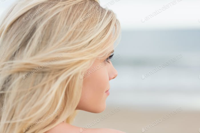 Close up side view of a relaxed young blond at the beach