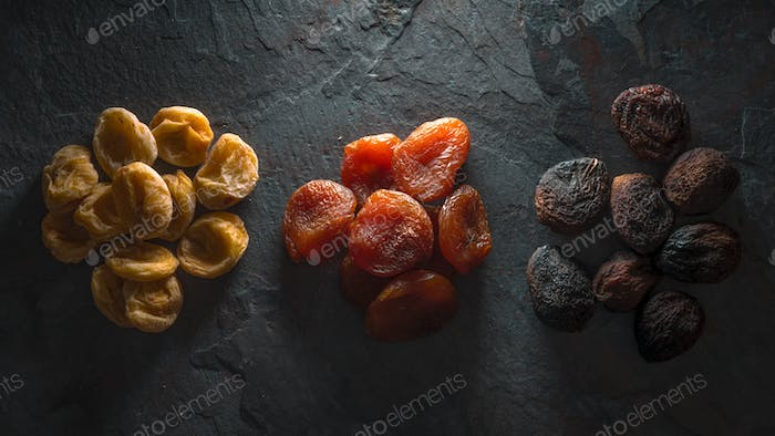 Multicolored dried apricots on a gray stone