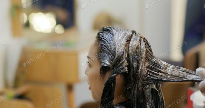 Frau färben ihre Haare im Friseursalon
