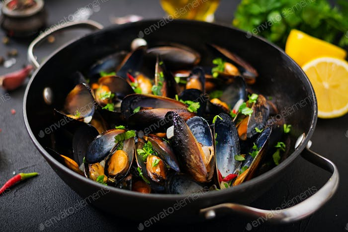 Mussels cooked in wine sauce with herbs in a frying pan on a black background.