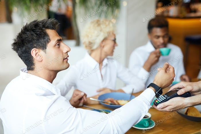 Young manager paying for lunch with smartwatch