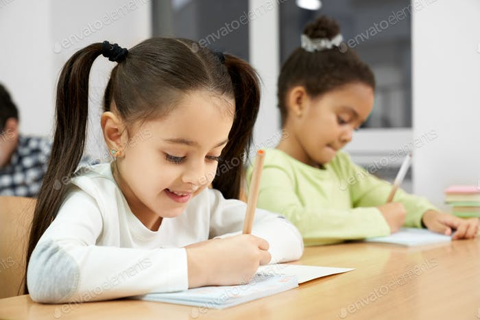 Pretty girls sitting at desk in class, writing in copybook