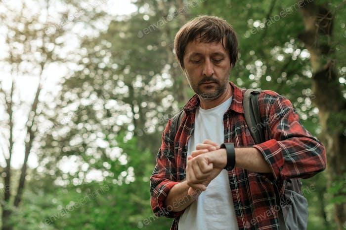 Умные часы на мужской пешеходной руке во время походов в лесу