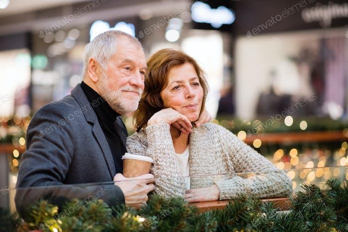 A tired senior couple doing Christmas shopping.