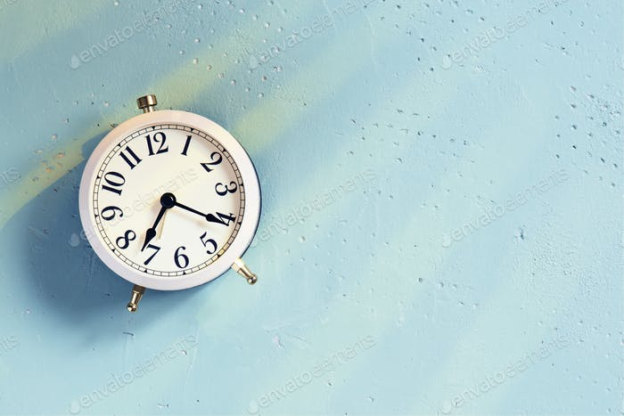 Blue Sunny Background with Alarm Clock