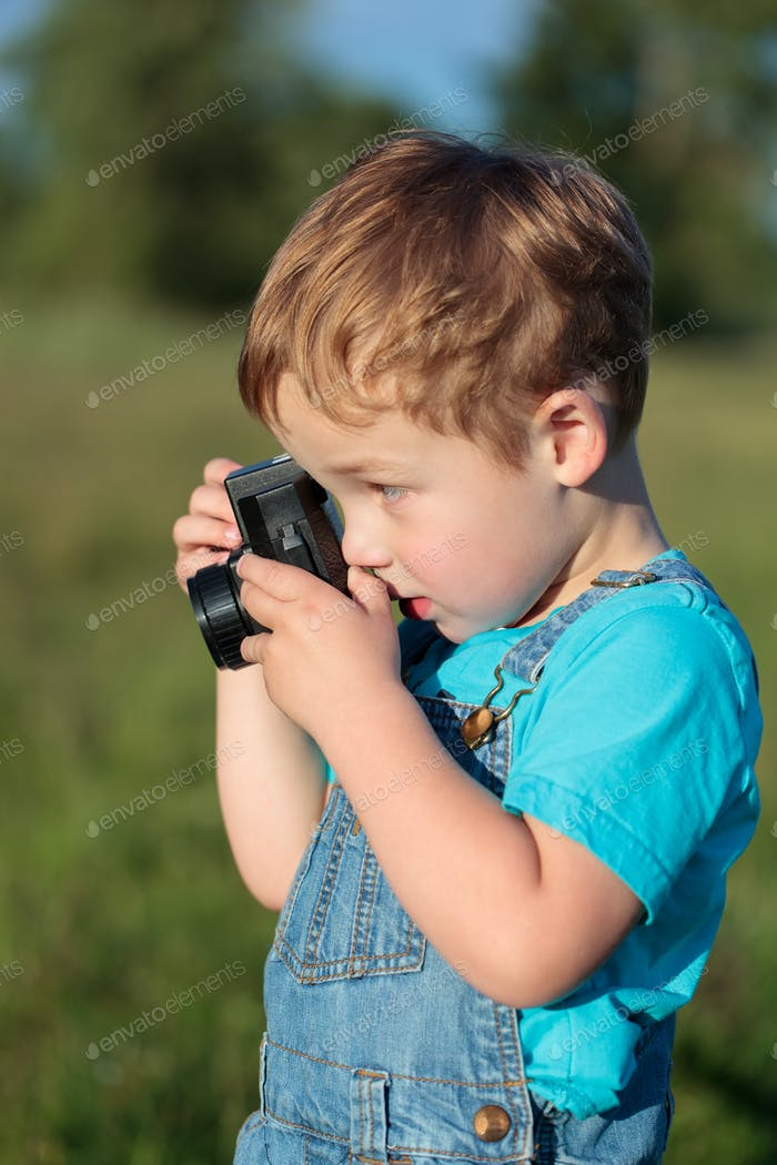 Little child taking pictures outdoor