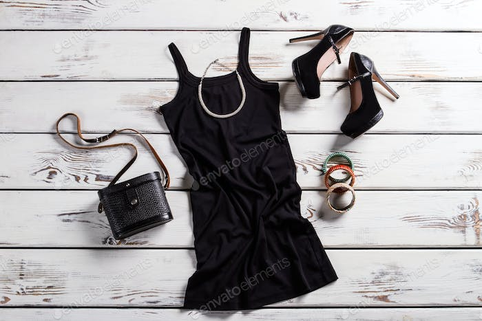 Black female outfit on table.