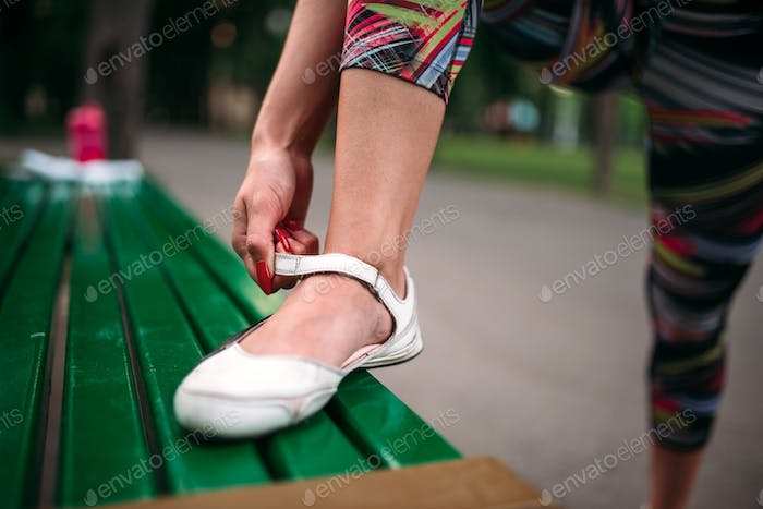 Sporty female person buttons footwear