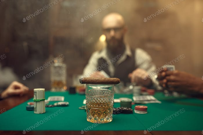 Whiskey and cigar on gaming table with green cloth