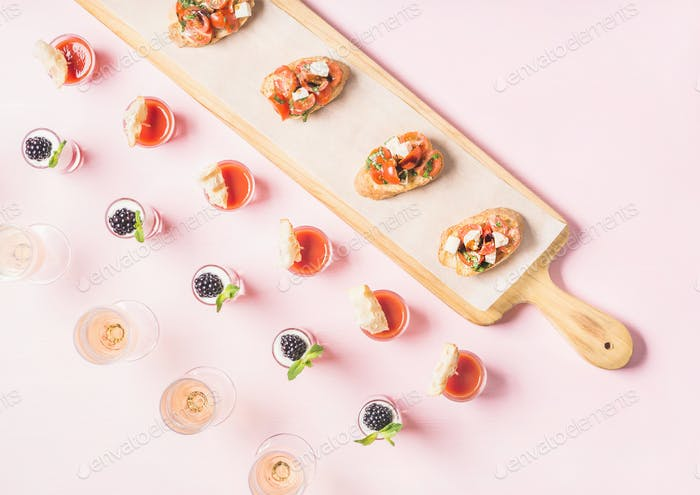 Snacks, brushetta sandwiches, gazpacho shots, desserts over pastel pink background