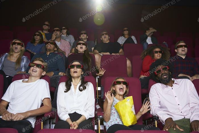 Audience In Cinema Wearing 3D Glasses Watching Horror Film