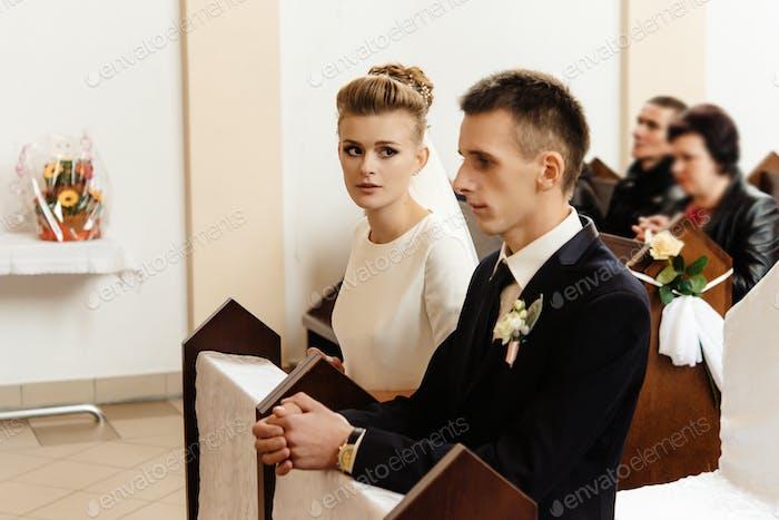 Braut und Bräutigam Vorbereitung auf die Kommunion auf Knien bei der Hochzeitszeremonie in der Kirche
