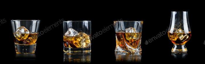 Set aus vier Glas Whisky mit Würfeleis auf schwarzem Hintergrund