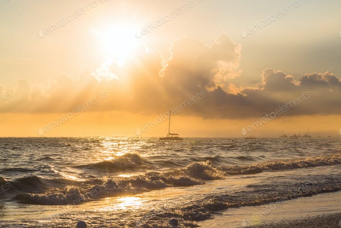 Boat and golden sunrise over ocean in Dominican Republic