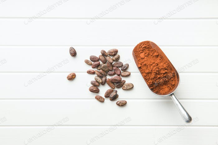 Dark cocoa powder in metal scoop and cocoa beans.