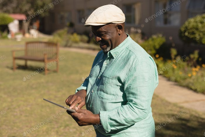 Side view of active senior man using digital tablet in the nursing park on sunny day