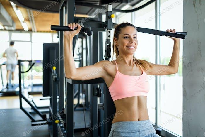 Happy Fit Fitness Frau trainiert auf Trainingsgerät im Fitnessstudio