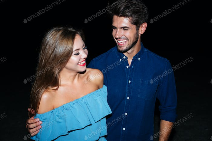 Cheerful young couple hugging and laughing together
