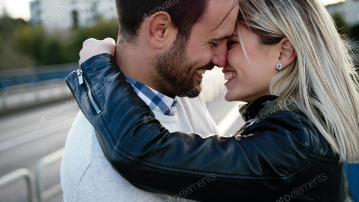 Romantic young happy couple kissing and hugging