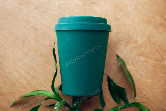 Stylish reusable eco coffee cup and leaves on wooden background