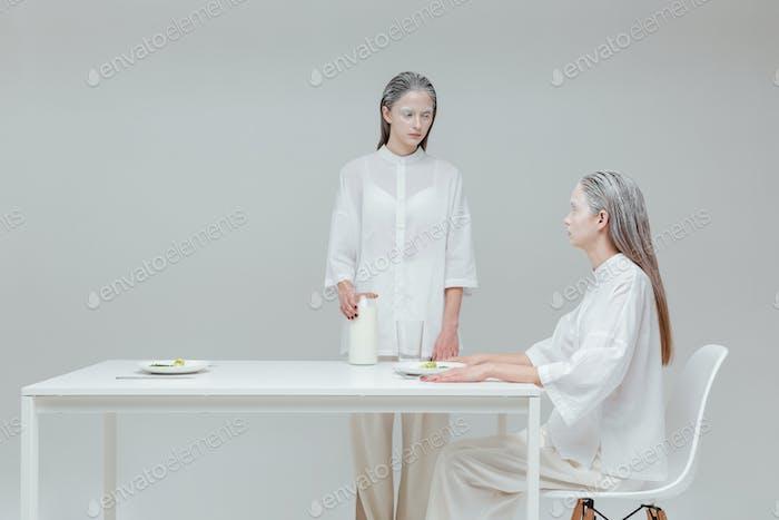 zwei Mädchen mit einer Mahlzeit am Tisch