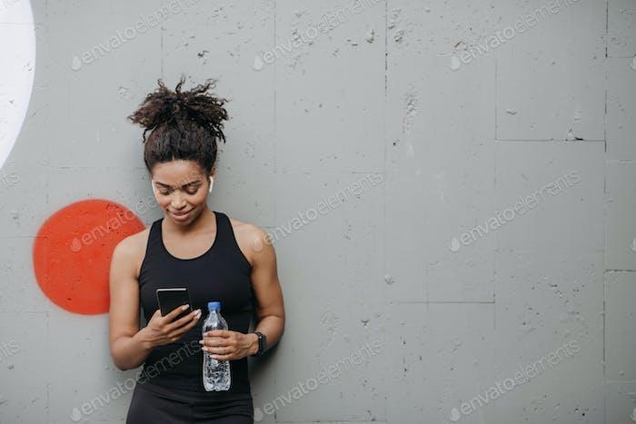 Musik und Sport. Frau mit Kopfhörern, Smart Watch und Flasche Wasser schaut auf Smartphone