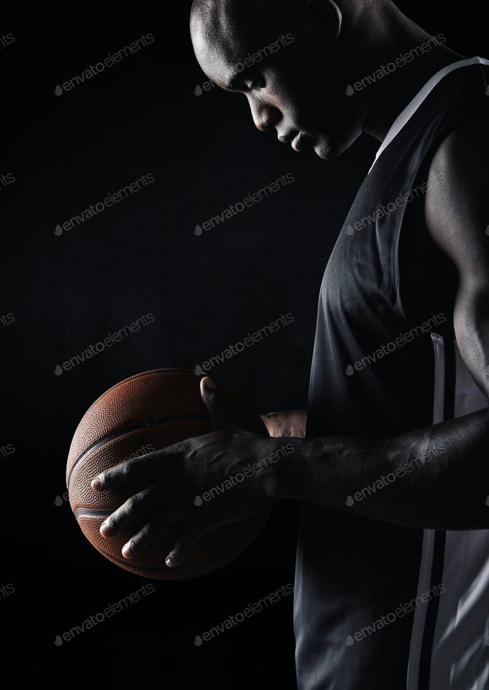 African sportsman holding basketball