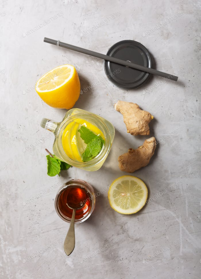 Ginger Water in Glass jar With Lemon and Honey on a Gray Concrete Background