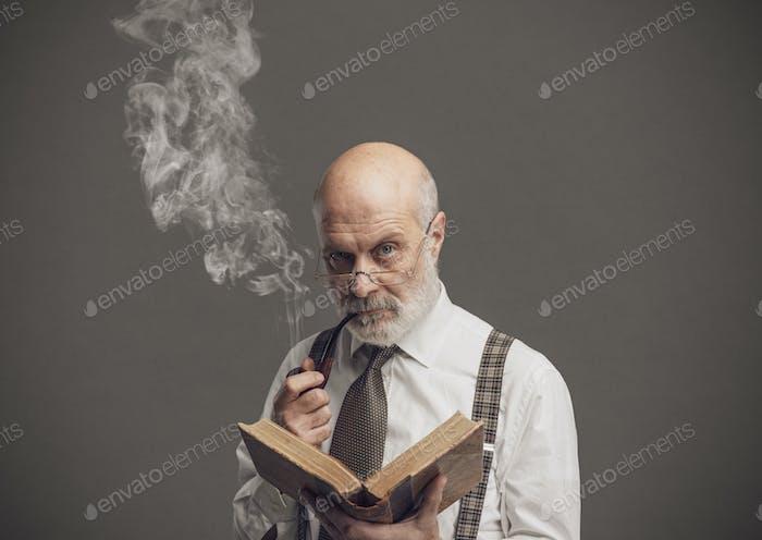Leitender akademischer Professor beim Lesen und Rauchen einer Pfeife