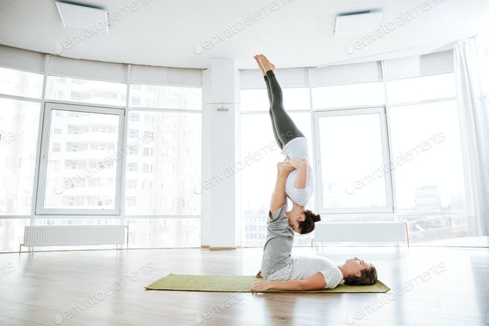 Beauiful couple practicing acro yoga on green mat