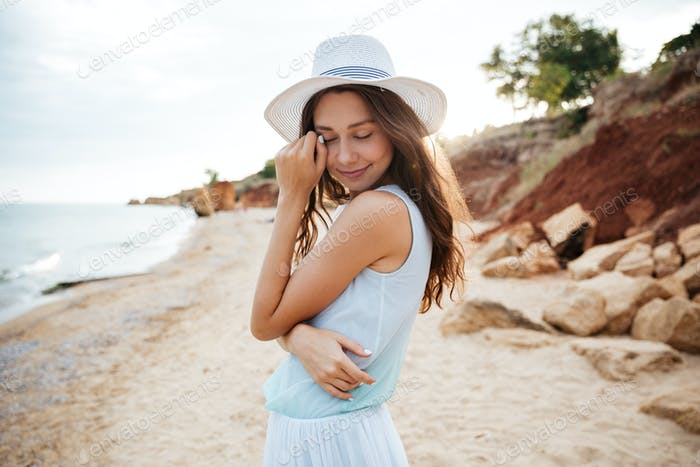 Sensual woman in white hat on the beach