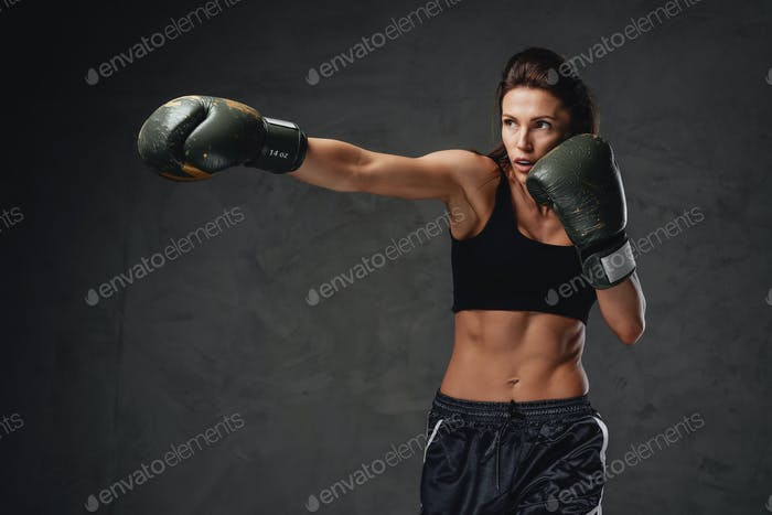 Fitness woman wearing boxing gloves and activewear