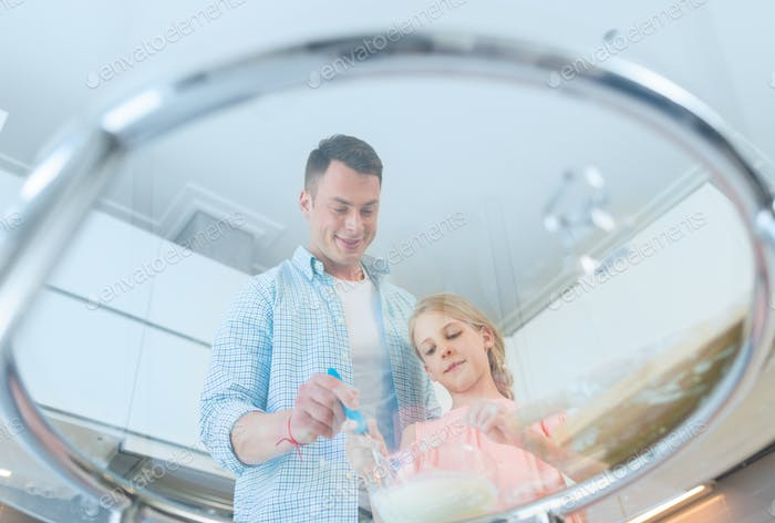 Dad and daughter preparing a cake in the kitchen