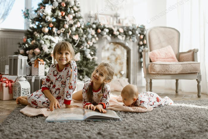 Two little sisters and a tiny brother lie on the carpet and read