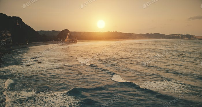 Rock ocean shore sunset with waves at water surface in aerial view. Epic nobody nature scenery