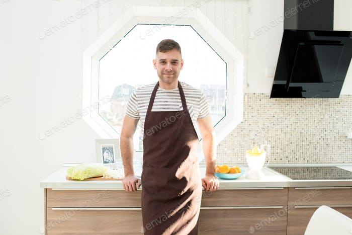 Positive guy wearing apron in domestic kitchen