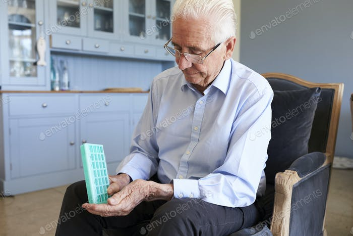 Senior Man At Home Using Pill Organiser For Medication