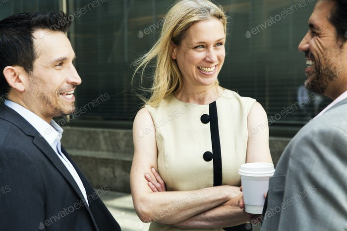Businesswoman and two businessman standing outdoors, chatting and smiling.