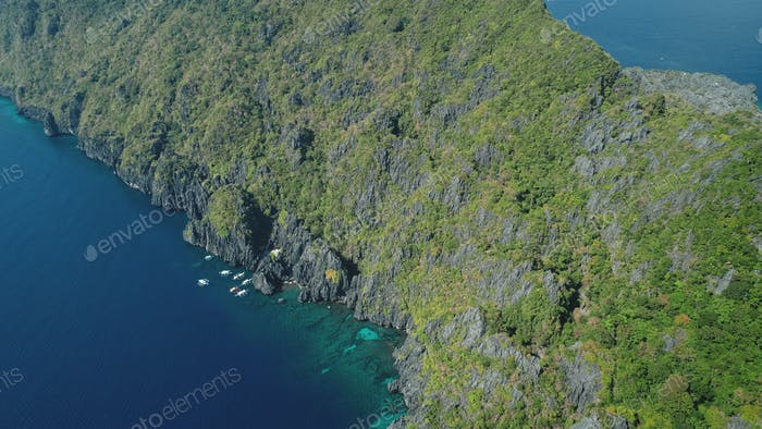 Green rock coast of tropic mountain island at ocean bay aerial. Nobody seascape with tropical nature