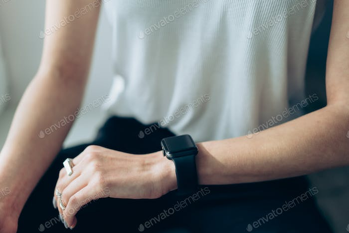 Slender girl with a smart clock on her arm