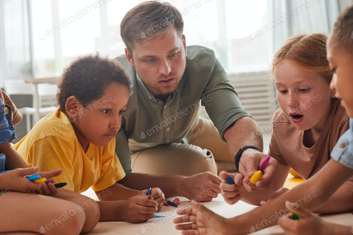 Children Drawing on Floor in Preschool