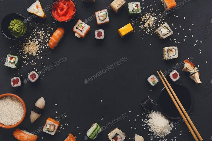 Japanese sushi and rolls on black background, copy space