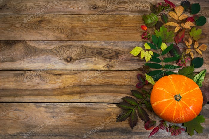 Fondo de Acción de Gracias con hojas y calabaza en la vieja mesa