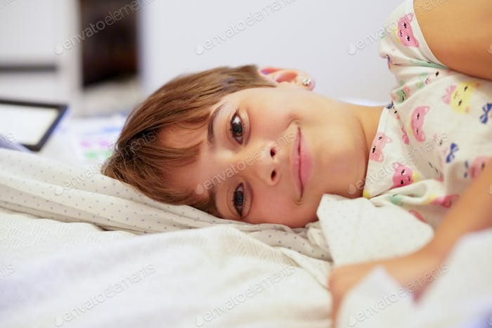 Little girl, eight years old, lying on her bed