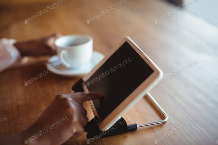 Hands of woman using digital tablet while having coffee